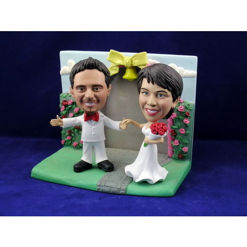 Photo 1 of Bride and Groom Arms Outstretched With Rose Garden Frame Bobblehead
