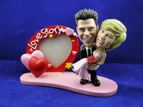 Groom Carries Bride With Heart Frame Bobblehead - Bobbleheads.com